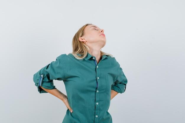 Jovem, vestindo a camisa verde, sofrendo de dor nas costas e parecendo cansada.