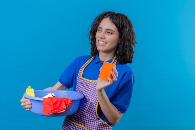 Jovem vestindo avental segurando a bacia com ferramentas de limpeza, mostrando a esponja na mão sorrindo alegre olhando de lado por cima da parede azul