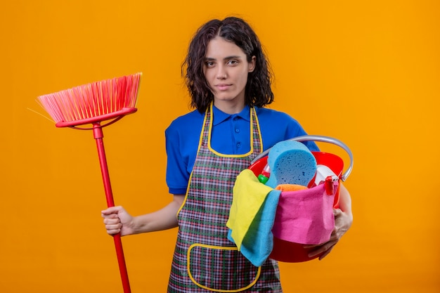 Jovem vestindo avental segurando balde com ferramentas de limpeza e esfregão com expressão confiante séria sobre parede laranja