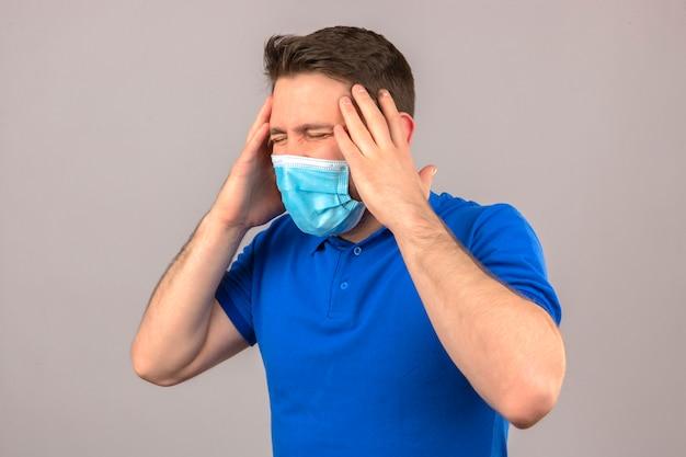 Jovem vestindo camisa polo azul em máscara protetora médica olhando doente e doente em pé com a mão na cabeça, sofrendo de dor de cabeça sobre parede branca isolada