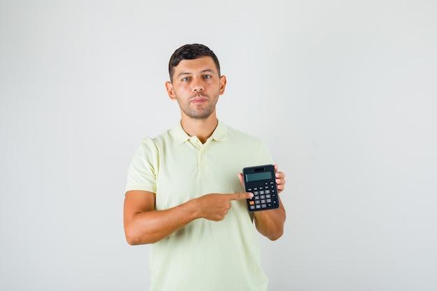Jovem vestindo camiseta com calculadora na mão