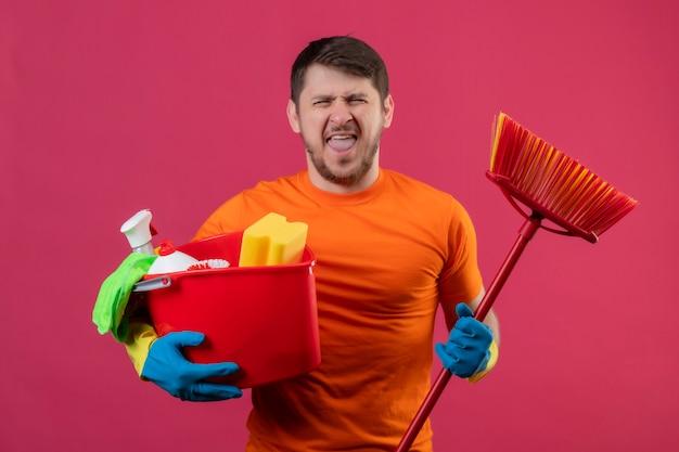 Jovem vestindo camiseta laranja e luvas de borracha segurando um balde com ferramentas de limpeza e esfregão