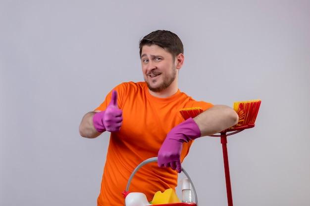 Jovem vestindo camiseta laranja e luvas de borracha segurando um balde com ferramentas de limpeza e um esfregão positivo e feliz sorrindo mostrando os polegares em pé sobre uma parede branca