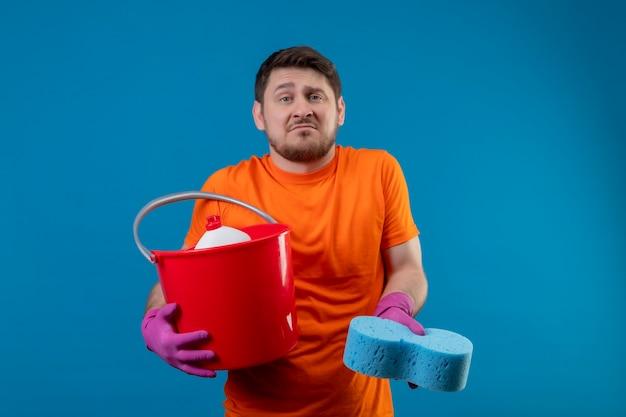 Jovem vestindo camiseta laranja e luvas de borracha segurando um balde com ferramentas de limpeza e uma esponja