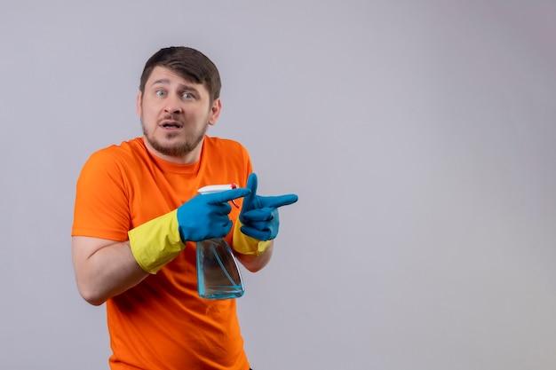 Jovem vestindo camiseta laranja e luvas de borracha segurando um spray de limpeza preocupado, apontando com os dedos para o lado