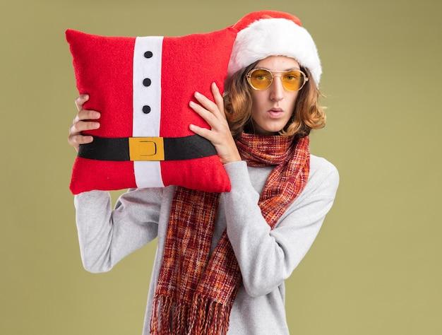 Jovem vestindo chapéu de papai noel de natal e óculos amarelos com um lenço quente no pescoço segurando uma almofada de natal, confuso em pé sobre uma parede verde