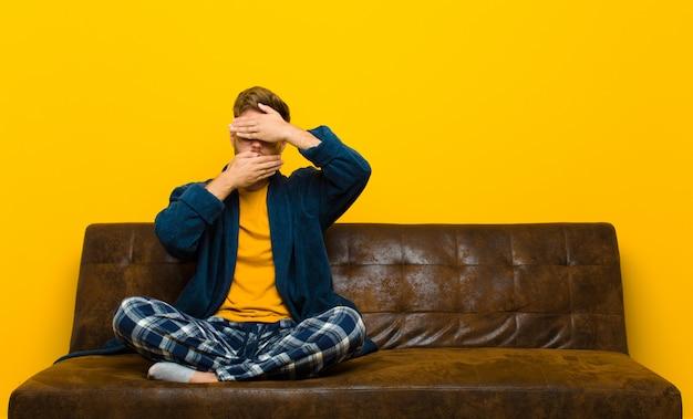 Jovem vestindo pijama cobrindo o rosto com as duas mãos dizendo não! recusando fotos ou proibindo fotos. sentado em um sofá
