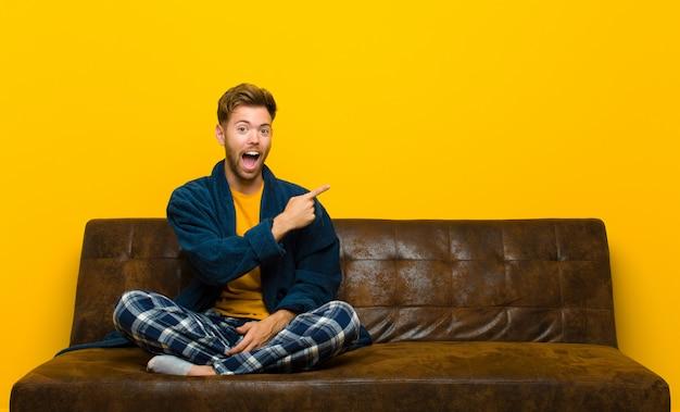 Jovem vestindo pijama olhando animado e surpreso apontando para o lado e para cima para copiar o espaço. sentado em um sofá
