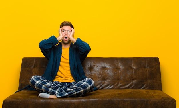 Jovem vestindo pijama olhando desagradavelmente chocado, assustado ou preocupado, boca aberta e cobrindo os dois ouvidos com as mãos. sentado em um sofá