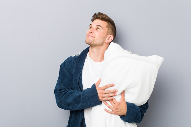 Jovem vestindo pijama segurando um travesseiro, olhando de soslaio com expressão duvidosa e cética.