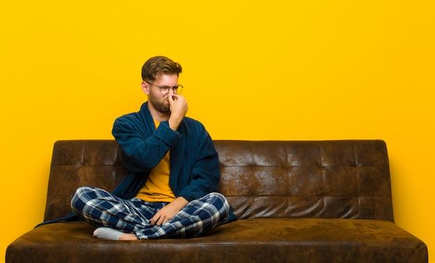Jovem vestindo pijama sentindo nojo, segurando o nariz para evitar cheirar um fedor sujo e desagradável