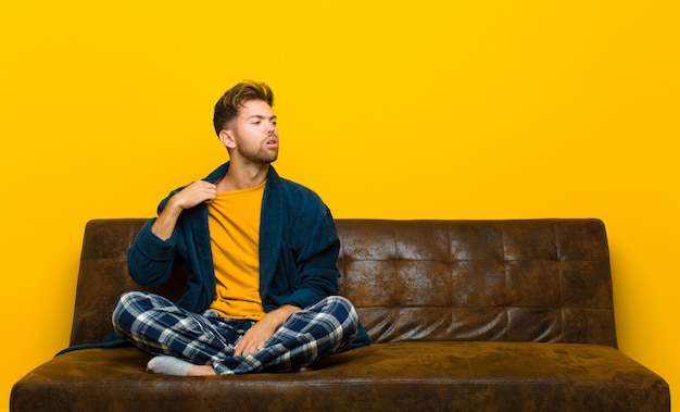 Jovem vestindo pijama, sentindo-se estressado, ansioso, cansado e frustrado, puxando o pescoço da camisa, olhando frustrado com o problema. sentado em um sofá