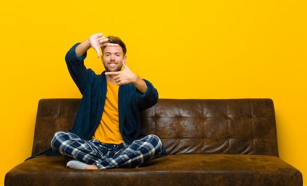 Jovem vestindo pijama, sentindo-se feliz, amigável e positivo, sorrindo e fazendo um retrato ou moldura com as mãos. sentado em um sofá