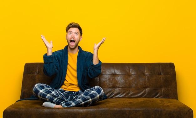 Jovem vestindo pijama, sentindo-se feliz, espantado, sortudo e surpreso, comemorando a vitória com as duas mãos no ar