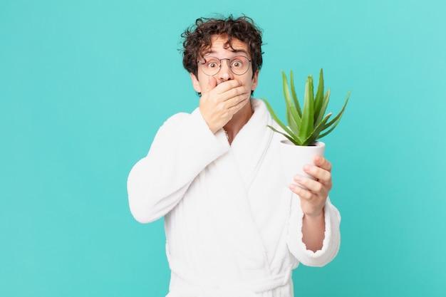 Jovem vestindo roupão de banho cobrindo a boca com as mãos com um choque