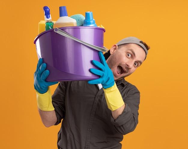 Jovem vestindo roupas casuais e boné com luvas de borracha, segurando um balde com ferramentas de limpeza, parecendo feliz e animado em pé sobre a parede laranja
