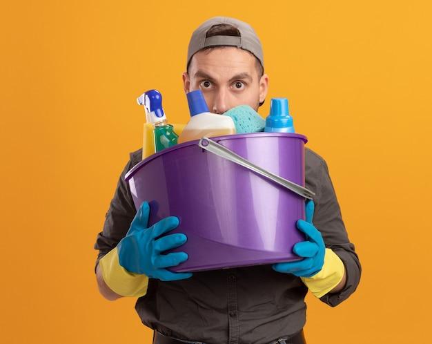 Jovem vestindo roupas casuais e boné com luvas de borracha, segurando um balde com ferramentas de limpeza, parecendo sério em pé sobre a parede laranja