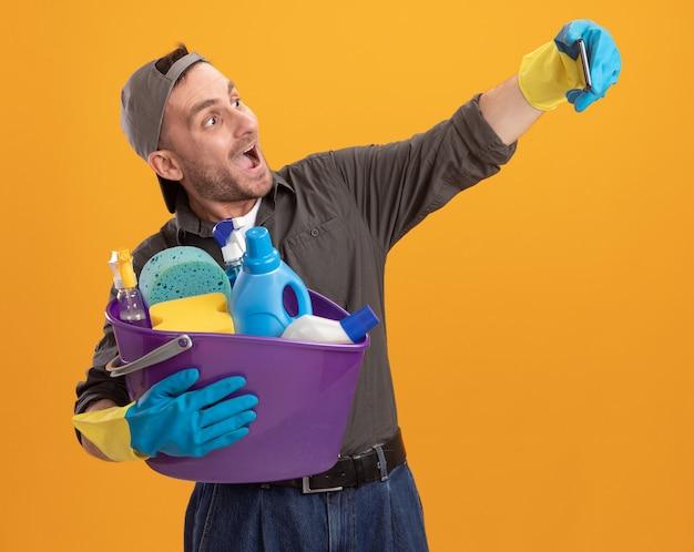 Jovem vestindo roupas casuais e boné com luvas de borracha, segurando um balde com ferramentas de limpeza, usando smartphone, fazendo selfie feliz e animado em pé sobre a parede laranja