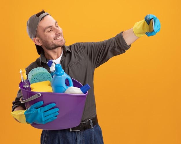 Jovem vestindo roupas casuais e boné com luvas de borracha, segurando um balde com ferramentas de limpeza, usando telefone celular, fazendo selfie sorrindo com uma cara feliz em pé sobre a parede laranja