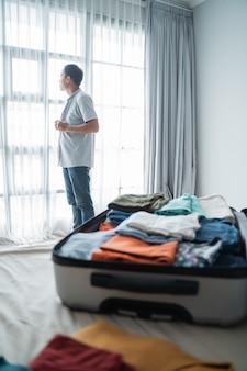 Jovem vestindo roupas depois de abrir a mala no quarto