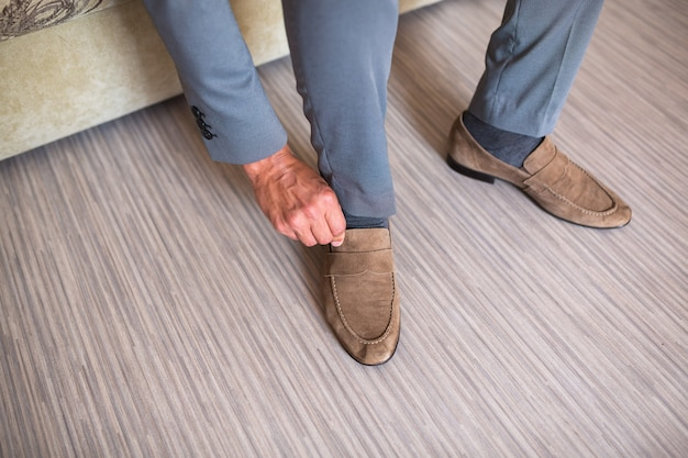Jovem vestindo sapatos de camurça marrom com terno e calça cinza. cara de hipster sentado com velhos sapatos elegantes. foco principal em atacadores