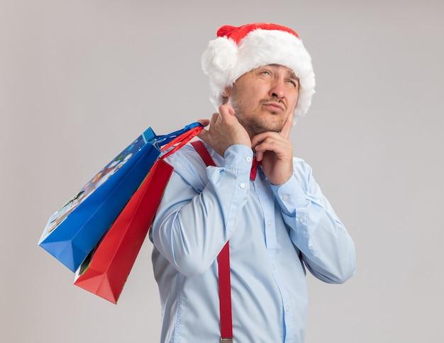 Jovem vestindo suspensórios gravata borboleta com chapéu de papai noel segurando sacolas de papel para presente, parecendo perplexo em pé sobre um fundo branco