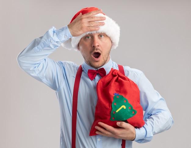 Jovem vestindo suspensórios gravata borboleta com chapéu de papai noel segurando uma sacola de papai noel cheia de presentes olhando para a câmera espantado e surpreso em pé sobre um fundo branco