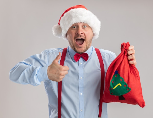 Jovem vestindo suspensórios gravata borboleta com chapéu de papai noel segurando uma sacola de papai noel cheia de presentes, olhando para a câmera, feliz e animado, mostrando os polegares em pé sobre um fundo branco