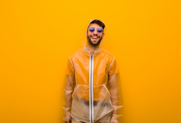 Jovem vestindo um casaco de chuva alegre com um grande sorriso