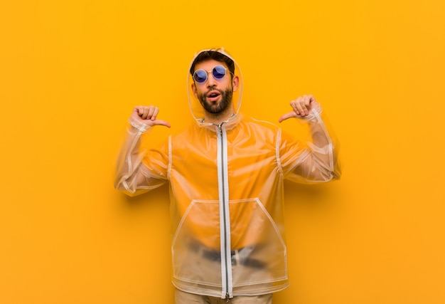Jovem vestindo um casaco de chuva, apontando os dedos, exemplo a seguir