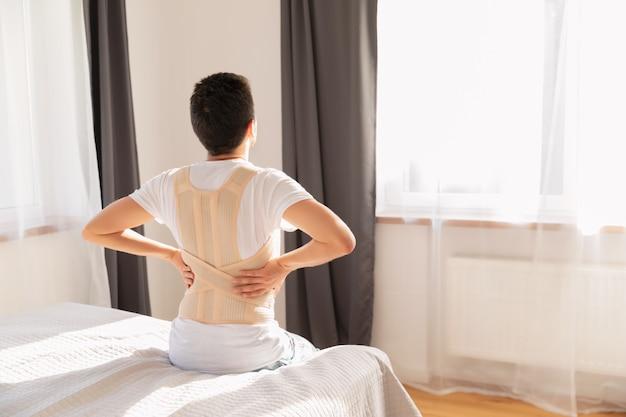 Jovem vestindo um cinto de apoio para as costas. aparelho lombar, suporte de costas para traumatismos nas costas ou tensão nas costas dos músculos.