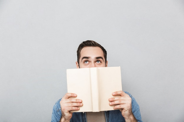 Jovem vestindo uma camisa isolada sobre uma parede cinza, cobrindo o rosto com um livro aberto