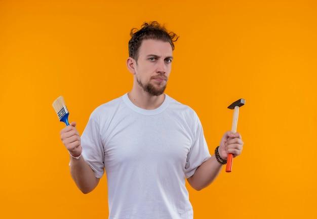 Jovem vestindo uma camiseta branca segurando um pincel e um martelo na parede laranja isolada