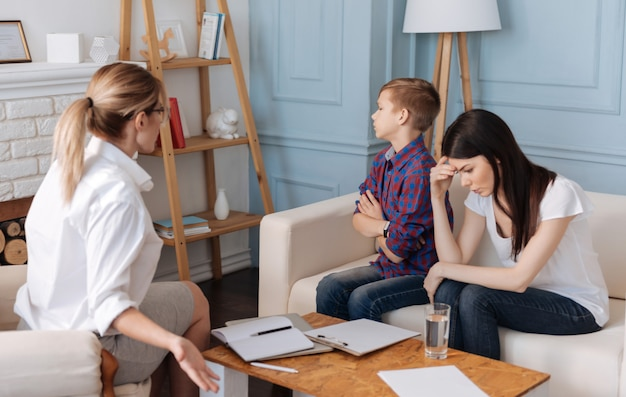 Jovem, vestindo uma camiseta branca, sentindo-se cansada durante uma consulta de psicoterapia