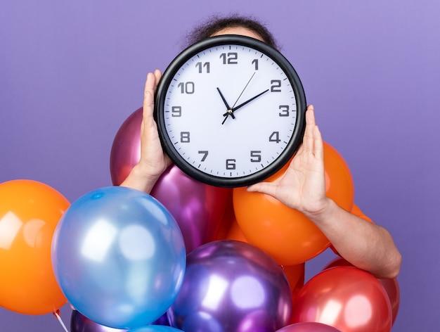 Jovem vestindo uma camiseta laranja em pé atrás de balões, coberto com um relógio de parede no rosto
