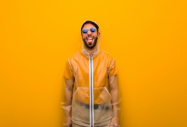 Jovem vestindo uma capa de chuva funnny e língua mostrando amigável