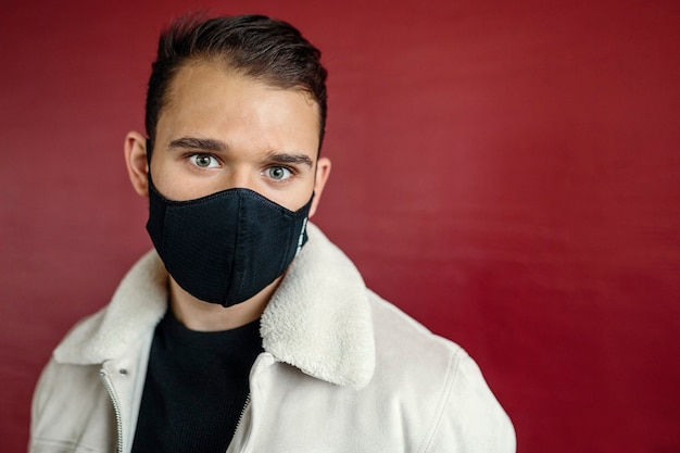 Jovem vestindo uma máscara preta, olhando para a câmera, sobre um fundo de parede vermelha na rua. conceito de juventude, moda e coronavírus. imagem com copyspace.