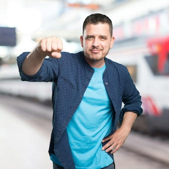 Jovem vestindo uma roupa azul. mostrando confiante de seu punho.
