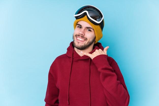 Jovem vestindo uma roupa de esqui, mostrando um gesto de chamada de telefone móvel com os dedos
