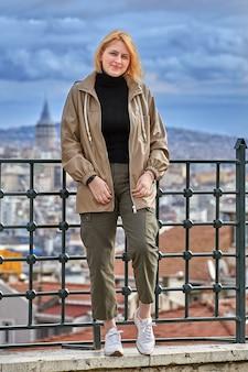 Jovem, viagem de inverno para istambul, posando em frente à paisagem urbana