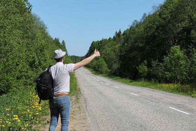 Jovem viaja com uma mochila em um dia de verão ao ar livre