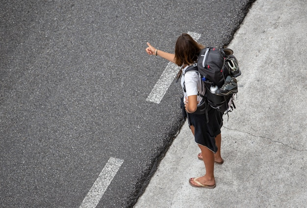 Jovem viaja pedindo carona perto de uma estrada