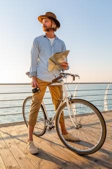 Jovem viajando de bicicleta à beira-mar nas férias de verão à beira-mar no pôr do sol, segurando um mapa turístico com a câmera