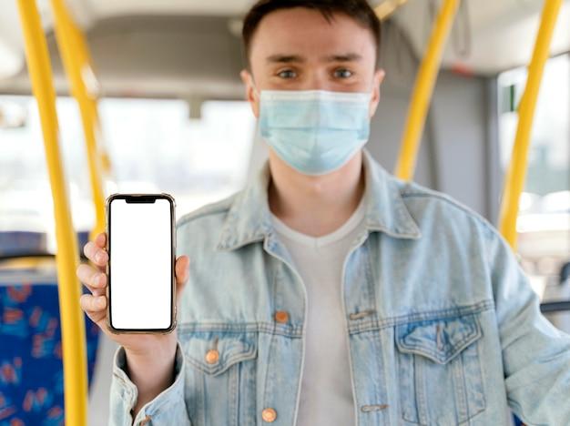 Jovem viajando de ônibus urbano mostrando smartphone com tela em branco