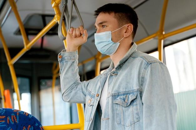 Jovem viajando de ônibus urbano usando máscara cirúrgica