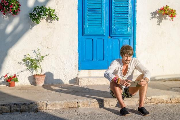 Jovem viajando em um país mediterrâneo, sentado no chão, lendo um conceito de tablet de trabalho nas férias de trabalho inteligente