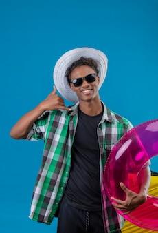 Jovem viajante afro-americano com chapéu de verão usando óculos escuros pretos segurando um anel inflável e sorrindo alegremente fazendo um gesto de me ligar
