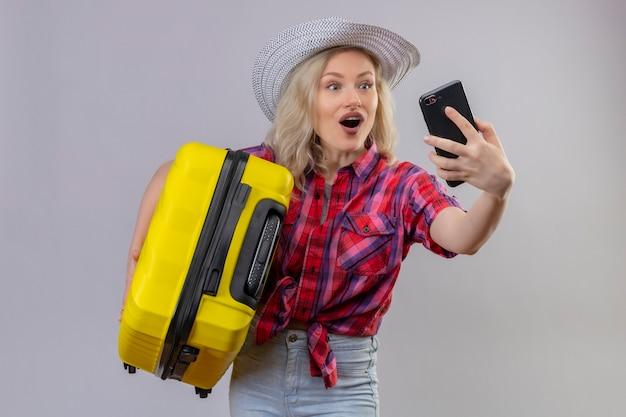 Jovem viajante alegre vestindo camisa vermelha e chapéu segurando mala e tirando selfie na parede branca isolada