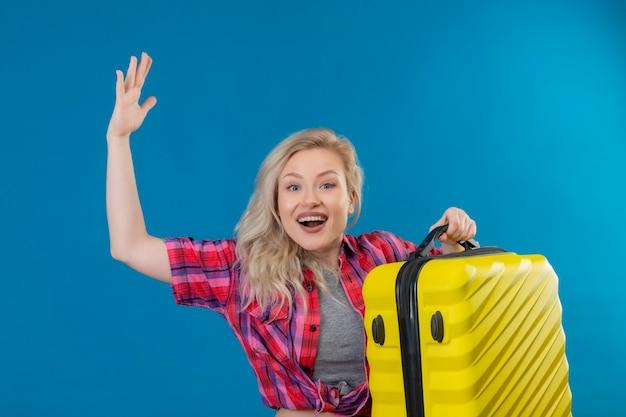 Jovem viajante alegre vestindo uma camisa vermelha, segurando uma mala com a mão levantada na parede azul isolada