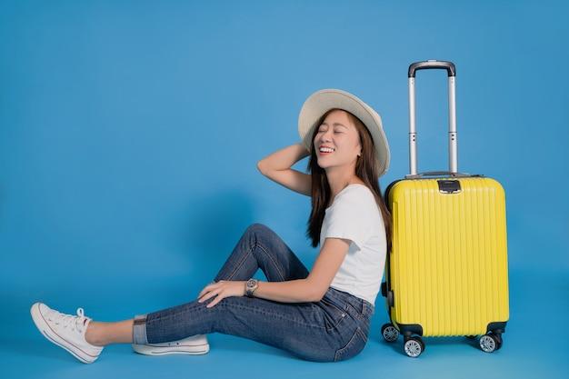 Jovem viajante asiática sorridente feliz sentado perto da mala amarela no azul Foto Premium